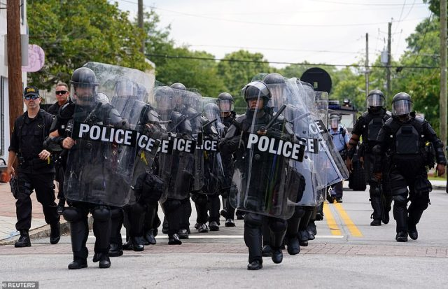 Police officers wore riot gear as they moved in to disperse crowds after fights broke out between groups