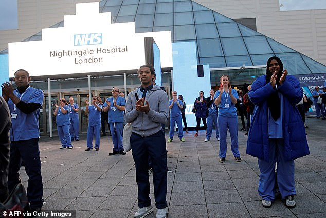 Medical staff and workers take part in a national 'clap for carers' to show thanks for the work of Britain's NHS (National Health Service) outside of the ExCeL London exhibition centre, which was transformed into the 'NHS Nightingale' field hospital