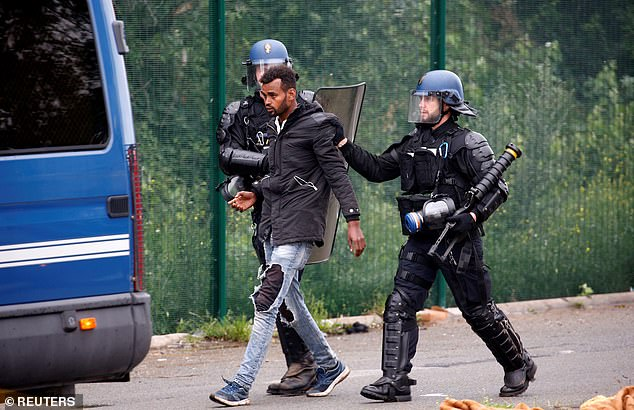 French police detain a migrant during dismantling of makeshift shelter camp in Calais, France