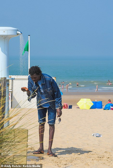 Even the swimming beaches – where migrants were never seen until recently – are no longer out of bounds as numbers here reach 1,200, twice as many as last summer. A migrant is seen using the beach shower onPlage de la Rotonde
