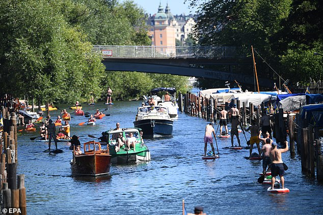 People enjoy boat rides, canoe paddling and stand up paddle in the nearly 30 degrees Celsius summer weather at the Palsund canal in Stockholm, Sweden in early August. The country has been unique for its liberal approach to the virus, avoiding locking the country down