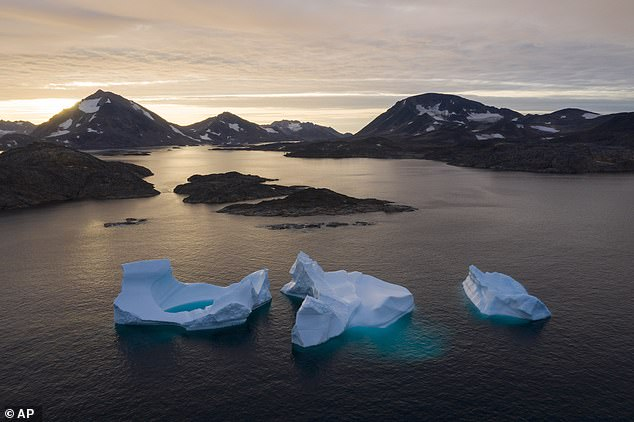 The heaviest rain in 70 years has fallen on Greenland's snowy summit, heightening fears about how rapidly the ice sheet is warming. Pictured, icebergs float away to sea near Kulusuk, Greenland, in this photo from 2019