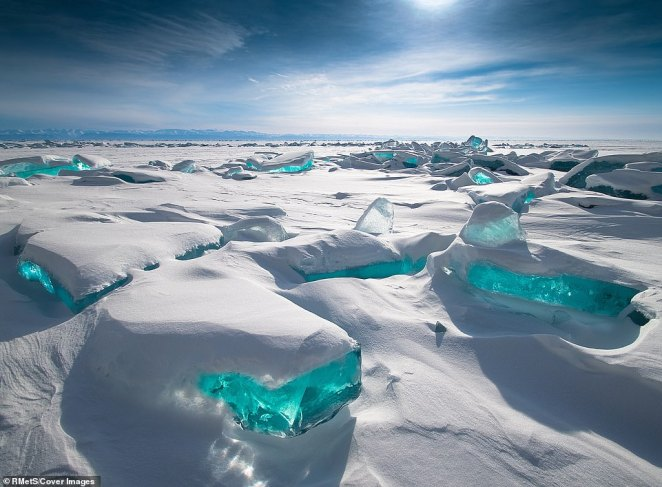 Lake Baikal Ice was photographed in the Russian Federation by Alexey Trofimov. The blue ice glistens from underneath a blanket of snow as the sun shines down on a clear day. The lake, thought to be the deepest in the world, is in the mountainous Russian region of Siberia, north of the Mongolian border