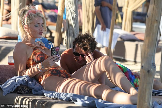 I've got a TEXT! Lottie was glued to her phone as she sat close to Ed on a shady lounger