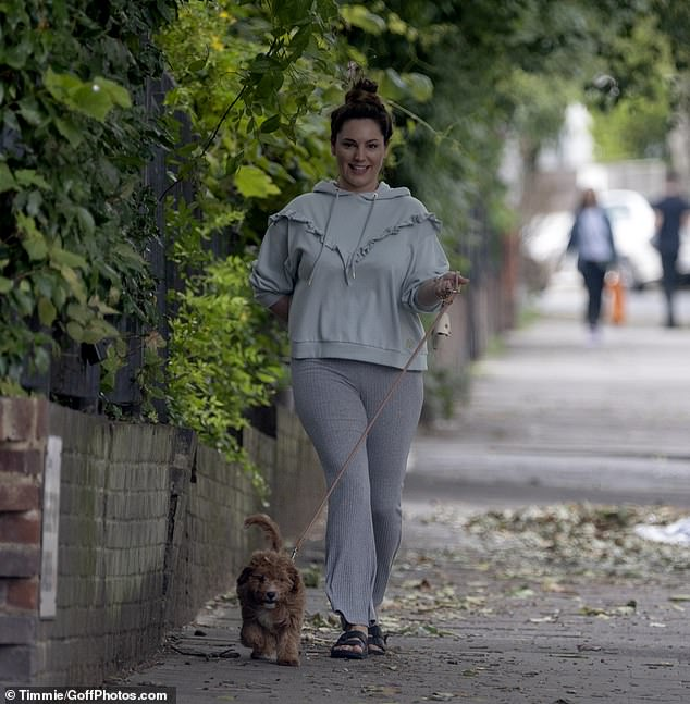 Perfect pooch: Kelly enjoyed an afternoon stroll around London on Saturday with her adorable dog Teddy