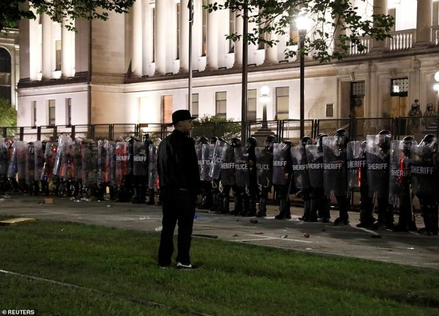 A man stood in front of law enforcement officers as they braced for a clash against protesters