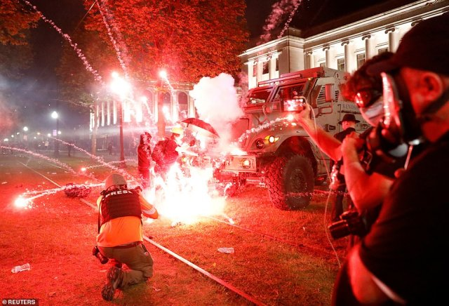 An explosive device detonates as a protester pushes back on an armored vehicle clearing the nearby park where crowds had gathered