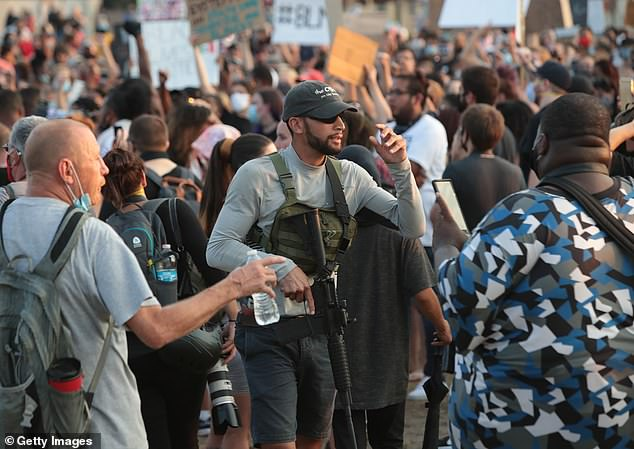 An armed protester takes part in a demonstration near the Kenosha County Court House on Monday