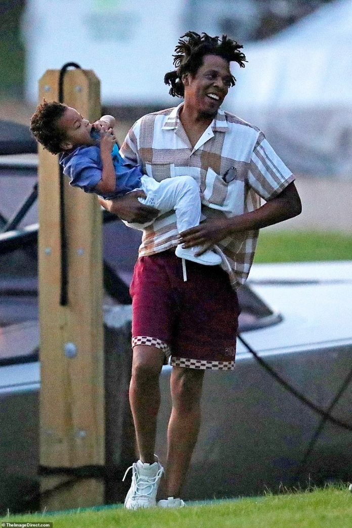 Handle!  Jay smiles as he holds his baby boy who appears to be trying to make his way out of his father's arms