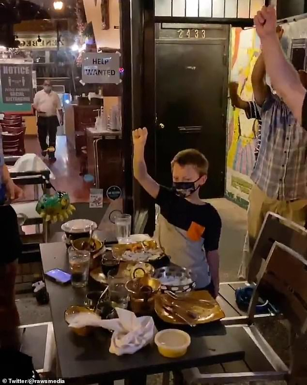 Some diners, including a young boy, were seen raising their fists after being approached by protesters at several outdoor restaurants in the entertainment precinct of Washington, D.C.