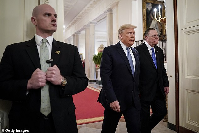 A Secret Service agent introduces himself as US President Donald Trump and retired Four-Star Army General Jack Keane arrive for a ceremony to present the Presidential Medal of Freedom to Keane in the East Room of the White House on March 10, 2020 in Washington, DC