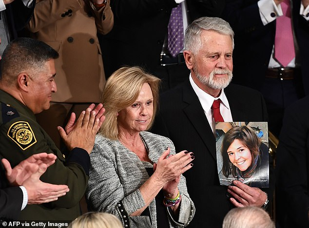 Carl Mueller (R) and Marsha Mueller (C) hold up a photo of their daughter Kayla, killed by ISIS while she was an aid worker in Syria, as they attended the State of the Union address at the US Capitol in Washington, DC on February 4, 2020