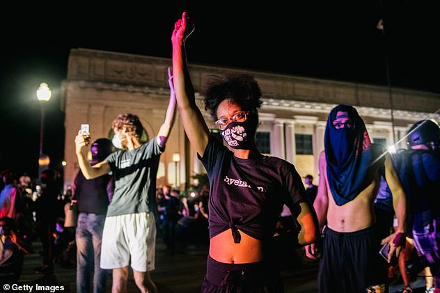 Peaceful demonstrators raise their fist in the air during protests last month in Kenosha, Wisconsin over the shooting of Jacob Blake