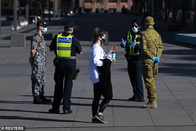 Mr Andrews said the state could not afford to lower restrictions and would extend the state of emergency to 18 months in September.  Pictured: A person wearing a face mask walks past Victoria Police, Air Force and ADF staff outside the Melbourne Museum