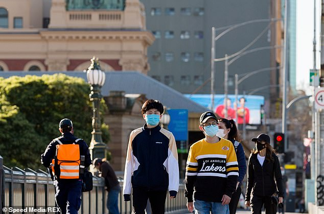The figures, confirmed by the Department of Health and Human Services on Sunday, bring the state's toll of the virus to 524 and the national total to 611 (in the photo, residents wearing face masks are walking in Melbourne on Saturday)