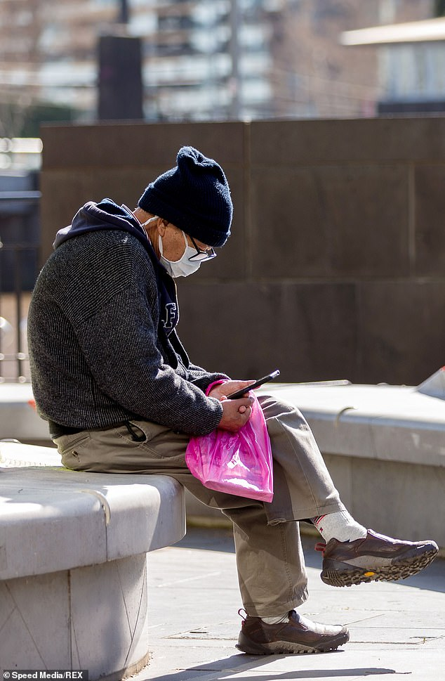 Health officials have said recommendations for face masks could stay in place for several more months (pictured, a Melburnian is sitting in the sun on Saturday)
