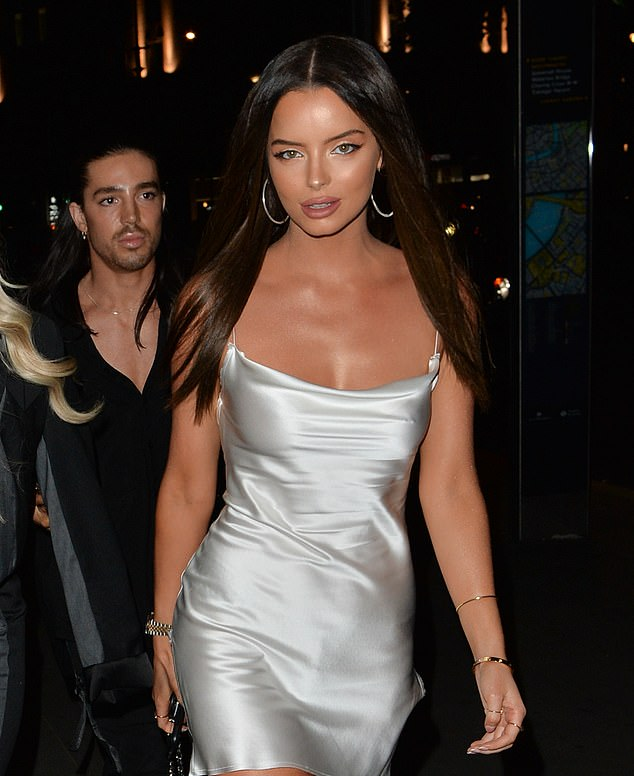 Racy!  The Love Island girl, 29, put on a very racy display in a tiny silver mini dress with a bold thigh-high slit