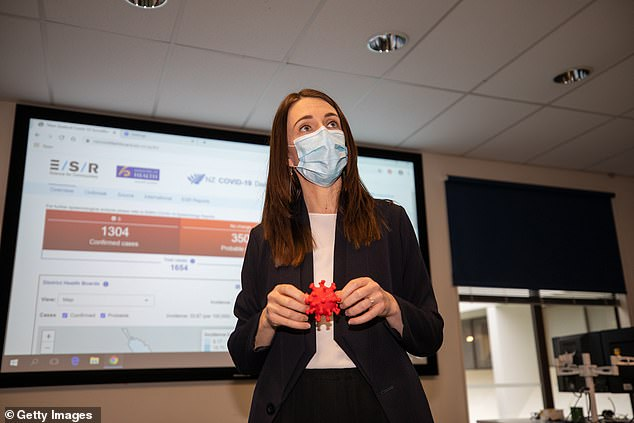 Ms Ardern holds a 3D model of a COVID-19 cell during a tour of a research facility inPorirua, north of Wellington on August 20. All Aucklanders in the city's south and west were told to get tested even if they did not have any coronavirus symptoms