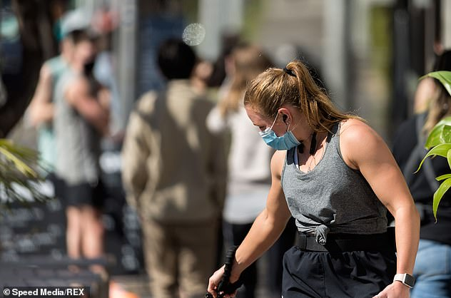 Melbourne residents are forced to wear masks when leaving home. Pictured: One resident pictured walking her dog on Saturday