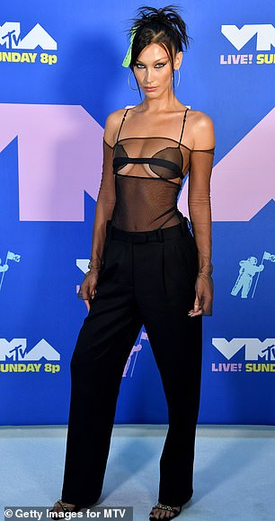 Hell on heels: She complemented the top with some high-waisted black slacks and a pair of black strappy stilettos with jeweled details