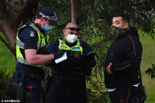 Case numbers in Victoria have been coming down in recent weeks. Pictured: Victorian Police speak a man in Dandenong, Melbourne
