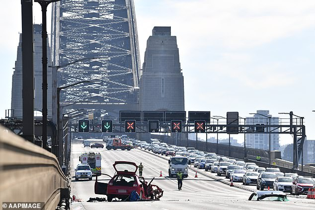One woman died and another had to fight for her life after a red Mitsubishi Mirage (pictured left) travelling north crashed head on into a BMW travelling south on the Harbour Bridge at 7:15am on Thursday