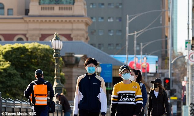 One expert says face masks in public should remain mandatory if lockdown is eased. Pictured are Melburnians soaking up the winter sunshine on Saturday