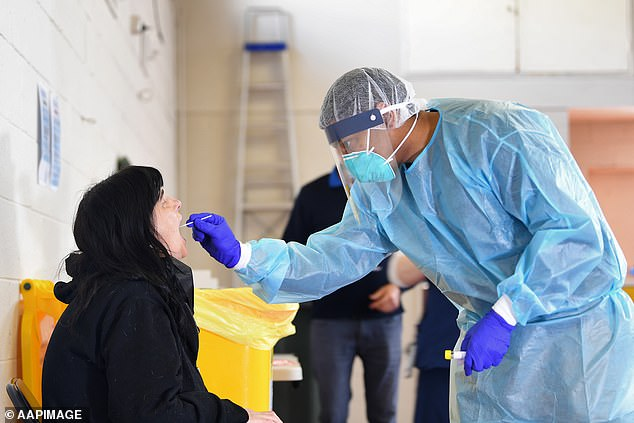 A healthcare worker conducts a coronavirus test on a patient in Melbourne on Sunday