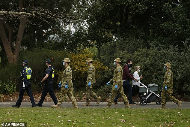 Pictured:ADF personnel and Victorian police officers are seen patrolling the Botanic Gardens in Melbourne