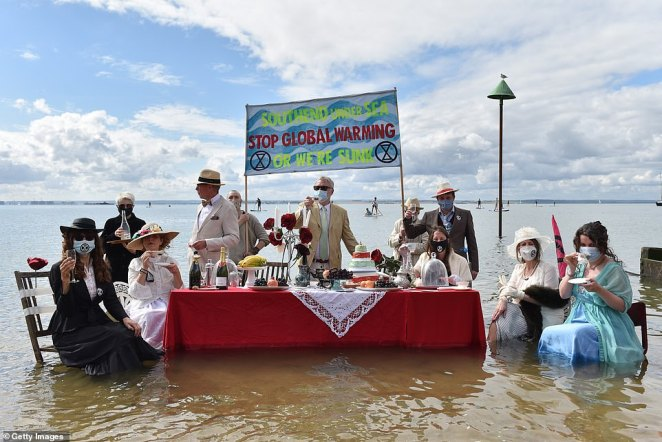 Extinction Rebellion protesters today staged a Titanic-themed dinner party in the sea to shine a light on rising sea levels