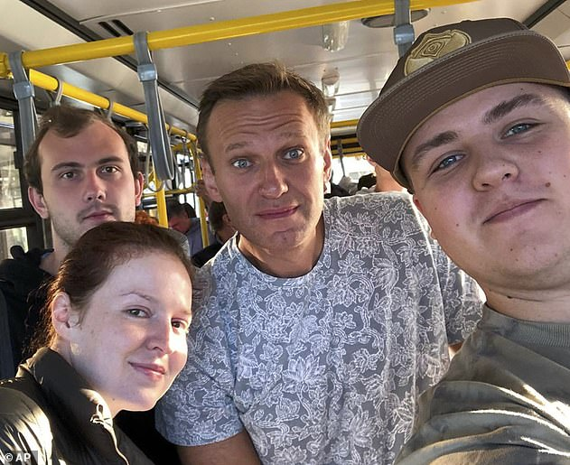 Russian opposition leader Alexei Navalny - pictured, centre, shortly before he fell ill on August 20 - is in a coma at a German hospital after allegedly being poisoned