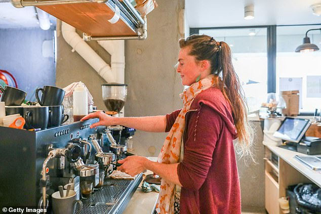 A study has found coffee lovers have lower risk of developing alcohol-induced cirrhosis (pictured, a barista makes coffee in Albert Park in Melbourne before Stage Four restrictions)
