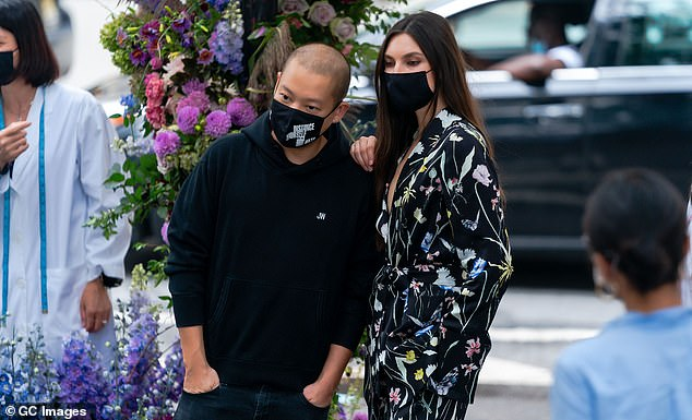 Blooming: The backdrop was decorated with a colorful floral arrangement scaling a street-post that complimented the jumpsuit and made for an industrial glam touch