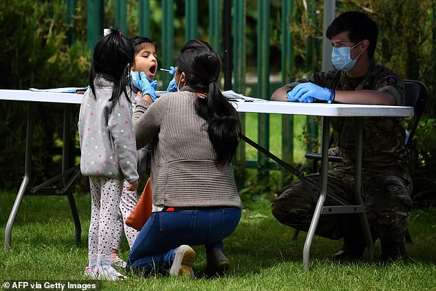Britons who show Covid symptoms can apply for drive-through tests, but some have revealed they are directed to centres more than 100 miles away (pictured: A family member administers a self-test to a child at a station in Leicester)