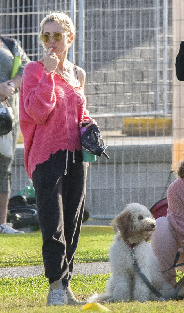 On a tight leash: The fluffy white dog sat patiently, watching the action, with Cristina holding onto its leash