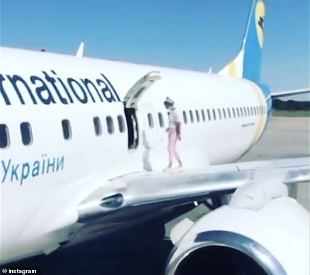 A woman climbed on to the wing of a plane after landing in Kyivon a flight from Antalya, bizarre video footage shows