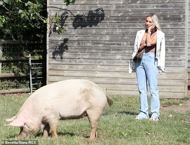 Farm life: Amber looked very unimpressed as she stared at a pig