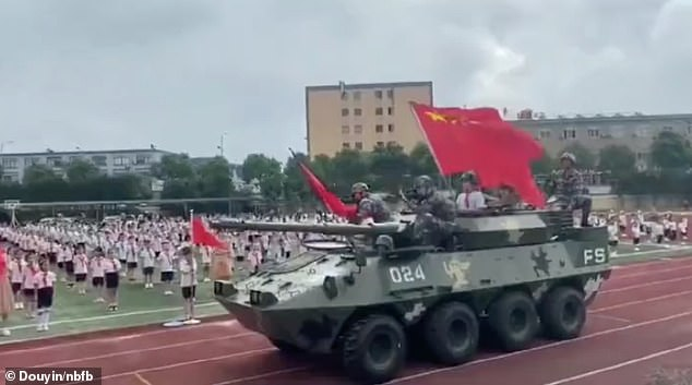 This is the dramatic moment a huge armoured fighting vehicle carrying weapon-equipped military personnel rolled past thousands of pupils during a school assembly in China