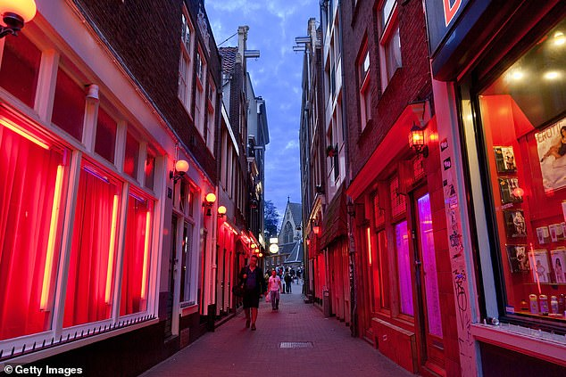 Ban of paid sex will be debated by cabinet in Netherlands today after Christian Democratic Appeal called for it to become a punishable offence (pictured, Amsterdam's red light district)