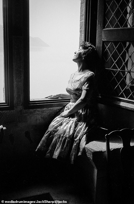 Unknown model looks out of a window at the beautiful Château de Chillon, Switzerland