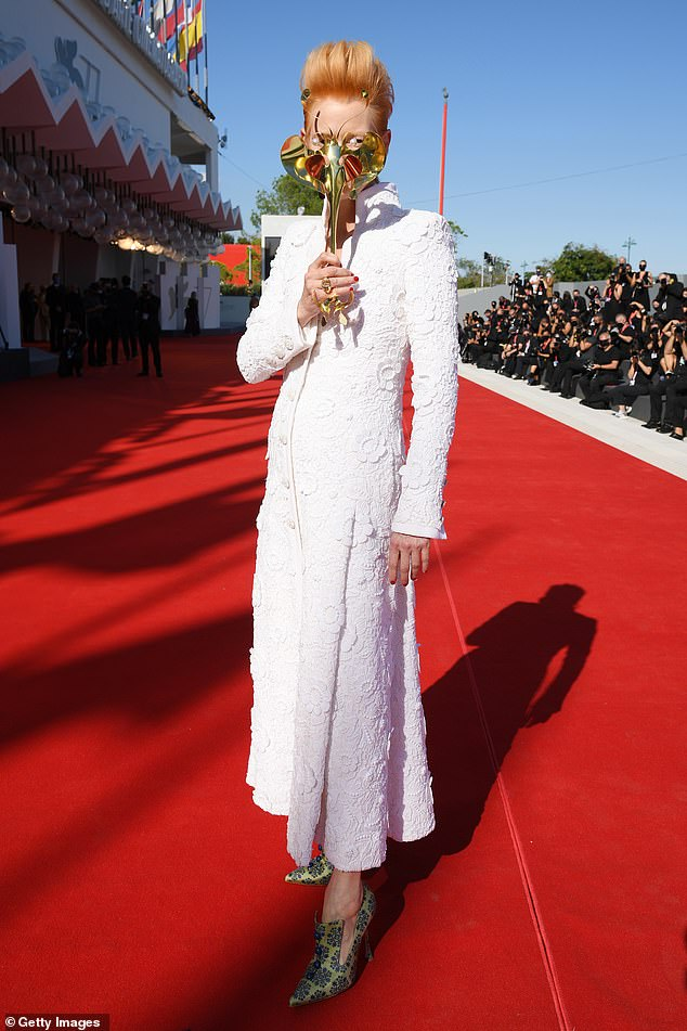 Festival:Tilda carried a gold Venetian mask with her as she walked the red carpet at the glamorous event