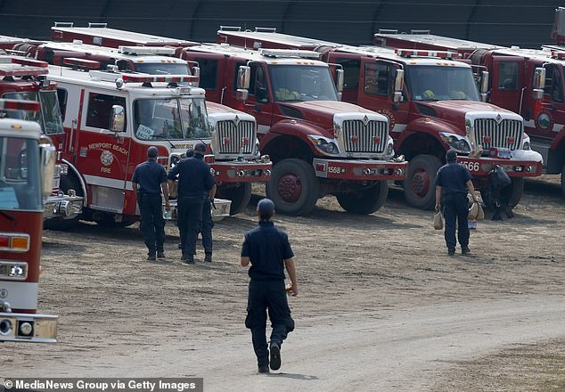 Firefighters head to their trucks with supplies at the LNU Lightning Complex Fire incident command center at the Calistoga Fairgrounds in Calistoga, California on August 25