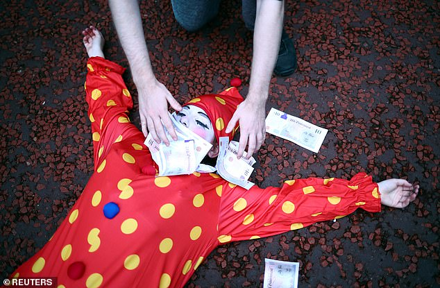 An activist wearing a clown costume is showered with fake money as she lies on the floor during today's London protests