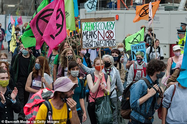 Hallam's controversial remarks were branded 'outrageous' by Conservative MPs as furious Extinction Rebellion activists took to Westminster today (pictured: Extinction Rebellion activists take part in a 'Carnival of Corruption' protest march in London, September 3, 2020)