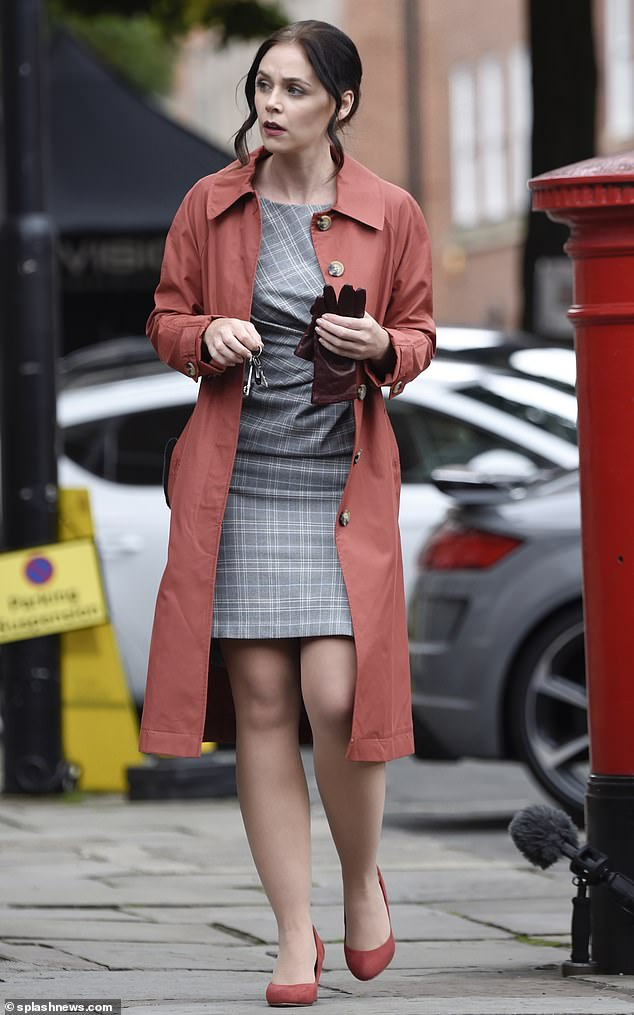 Stylish:Amy Wren was dressed in a more stylish ensemble including a smart grey dress and a salmon-coloured coat