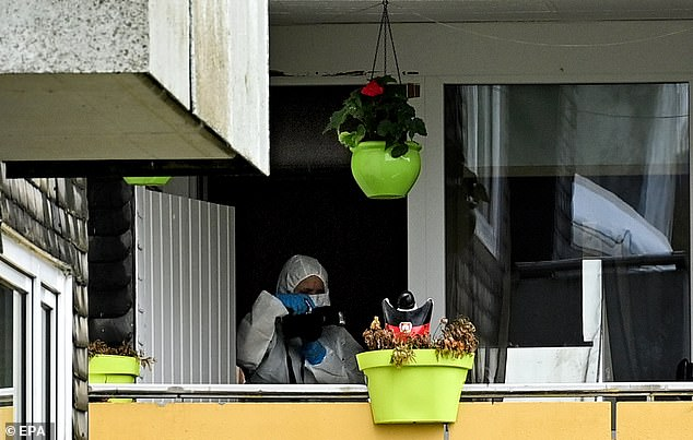 An investigator in forensic gear works on the balcony of the apartment building where a mother is suspected of having killed her five children