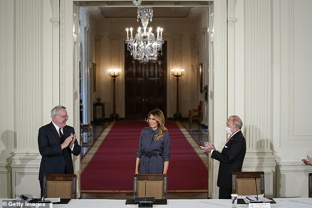 Melania Trump is welcome to the event byDirector of National Drug Control Policy James Carroll (left) and Larry Kudlow, President Trump's chief economic adviser (right)