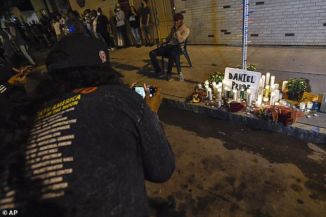 An activist stops to take a picture of a make-shift memorial for Daniel erected sometime on Wednesday evening