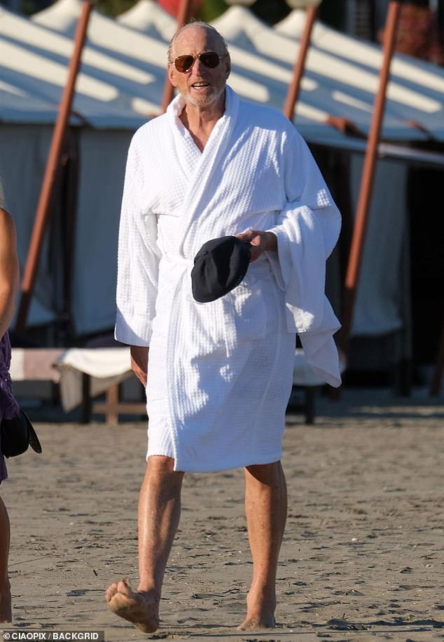 Suave: The Widow star covered his shirtless body as he strolled along the beach