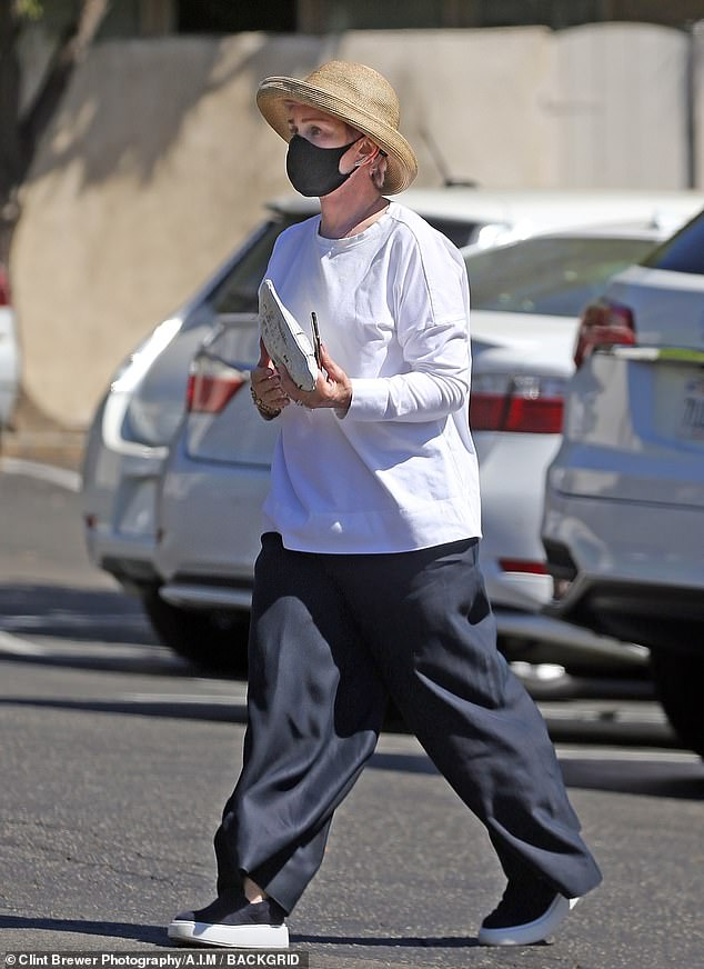 Baggy look:Sharon sported a black face mask and straw hat as she went about her shopping run, in an extremely baggy white top and dark trousers